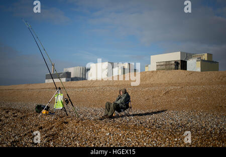 A fisherman sits outside Dungeness Power Station in Kent, England, Great Britain - Stock Photo