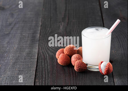 Glass of cold lychee juice on the old wooden table - Stock Photo