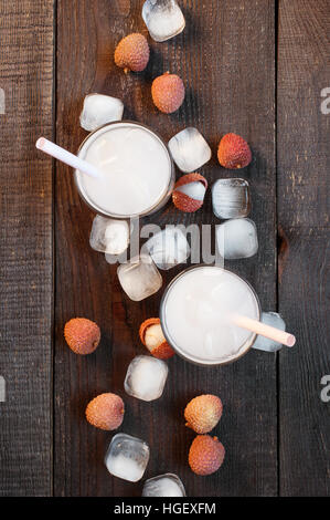 Two glasses of cold lychee juice on the old wooden table - Stock Photo