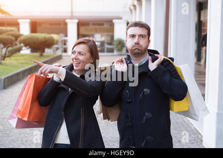 Man very bored of the shopping addiction of his girlfriend - Stock Photo