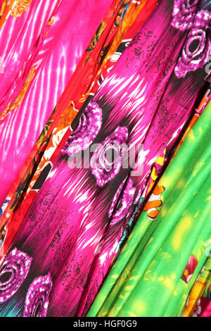 Bright multi colored printed fabrics with a Caribbean or Hawaiian beach style. - Stock Photo
