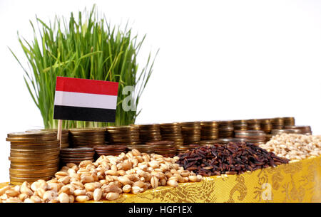 Yemen flag waving with stack of money coins and piles of wheat and rice seeds - Stock Photo