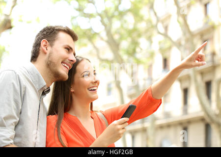 Happy couple searching home location with the mobile phone in the street with buildings in the background - Stock Photo