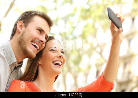 Happy casual couple taking selfie or photographing with a smart phone in the street - Stock Photo