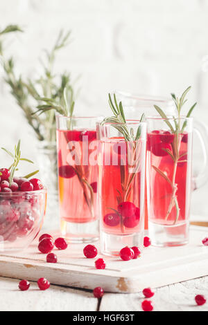 Refreshing drink with cranberries and rosemary on white wooden background, selective focus, copy space - Stock Photo