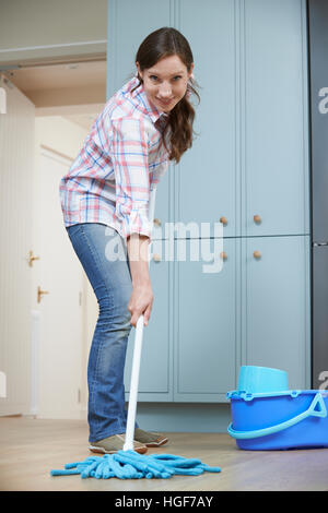 Woman Cleaning Kitchen Floor With Mop - Stock Photo