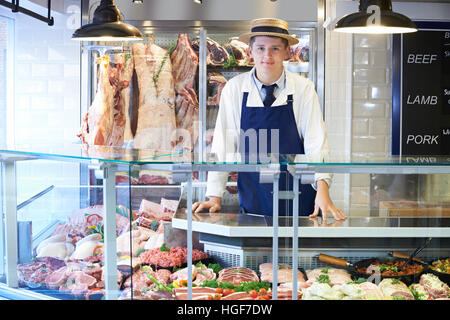 Portrait Of Butcher Standing Behind Counter - Stock Photo