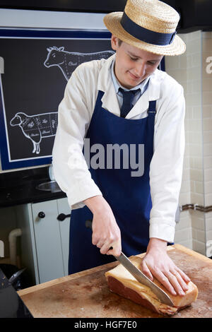 Trainee Butcher Preparing Sirloin Steak - Stock Photo