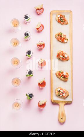 Various snacks, brushetta sandwiches, gazpacho shots, desserts over pink background - Stock Photo