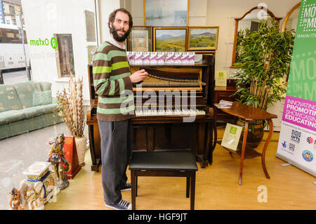 Pianist Matthew Bourne with an old upright piano in an Oxfam shop. - Stock Photo