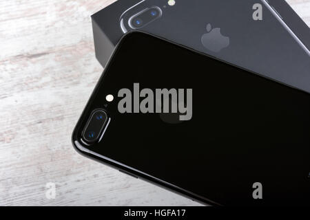 BURGAS, BULGARIA - DECEMBER 29, 2016: New Apple iPhone 7 Plus Jet Black, back side, on white wooden background. - Stock Photo