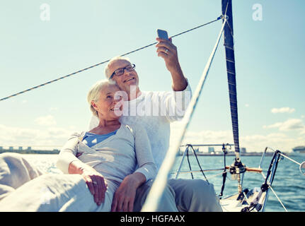 senior couple taking selfie by smartphone on yacht - Stock Photo
