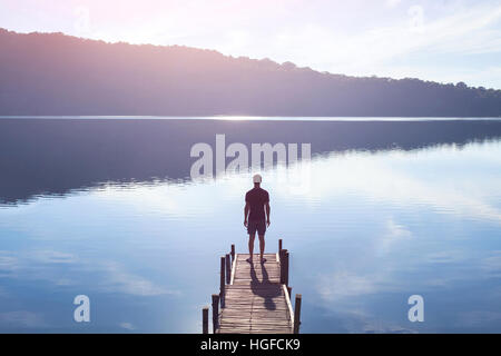 dreamer, silhouette of man standing on the lake wooden pier at sunset, human strength, psychology concept - Stock Photo