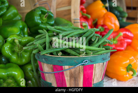 fresh green beans in wooden bushel basket and colorful peppers at the farmers market - Stock Photo