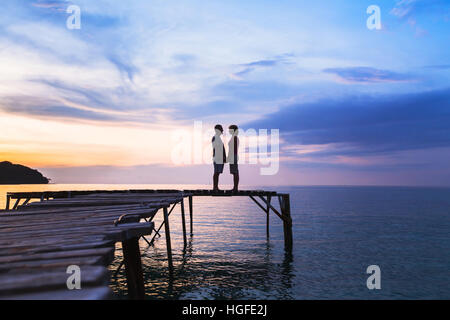 beautiful romantic love background, silhouette of affectionate couple on the pier at sunset beach - Stock Photo