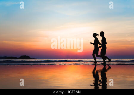 jogging and healthy lifestyle, two runners silhouettes on the beach at sunset, workout and sport - Stock Photo