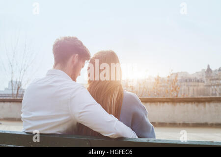 dating or first love, young couple sitting together on the bench, view from the back - Stock Photo