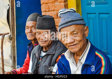 Beni, Nepal - circa May 2012: Three old men with caps on their heads sit on bench and smile to photocamera in Beni, - Stock Photo
