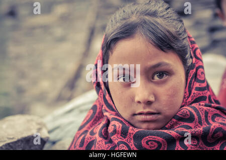 Beni, Nepal - circa May 2012: Young brown-haired girl wears red and black scarf with ornaments in Beni, Nepal. Documentary - Stock Photo