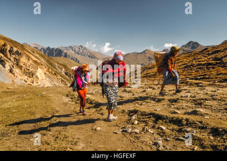 Dolpo, Nepal - circa May 2012: Native women with baskets on their backs walk up hill in mountainous region of Dolpo, - Stock Photo