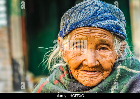 Beni, Nepal - circa May 2012: Photo of old woman with wrinkles and piercing wearing blue cap and looking to photocamera - Stock Photo