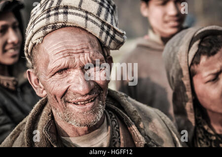 Dolpo, Nepal - circa May 2012: Old native man with little beard wears brown headcloth and jacket and frowns to photocamera - Stock Photo