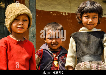 Beni, Nepal - circa May 2012: Three young native children pose to photocamera in Beni, Nepal. Documentary editorial. - Stock Photo