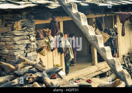 Dolpo, Nepal - circa May 2012: Two young children pose in their simple wooden house with stones at side in Dolpo, - Stock Photo
