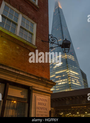 The Shard looms above the London Bridge Hospital on the south bank of the Thames, London, UK. - Stock Photo