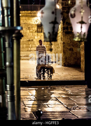 Jerusalem, Israel - November 1, 2013: Pilgrims enter the Church of the Holy Sepulchre with the lamps over the Stone - Stock Photo