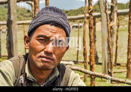 Beni, Nepal - circa May 2012: Native man with black knitted cap on his head in Beni, Nepal. In background with wooden - Stock Photo