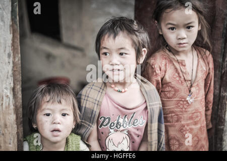 Beni, Nepal - circa May 2012: Three small sisters with brown hair and brown eyes pose to photocamera in front of - Stock Photo