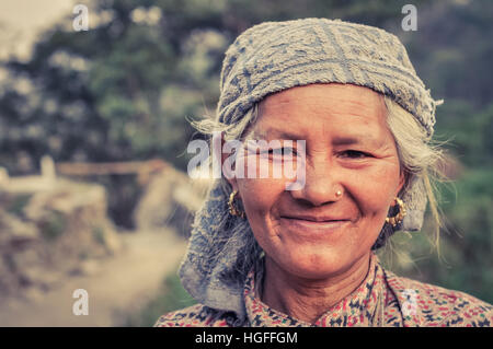 Beni, Nepal - circa May 2012: Native grey-haired woman with headcloth and golden earrings and piercing smiles nicely - Stock Photo