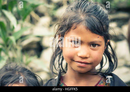 Beni, Nepal - circa May 2012: Young native girl with wet brown hair looks with her big brown eyes to photocamera - Stock Photo