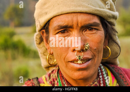 Dolpo, Nepal - circa May 2012: Native woman with brown headcloth has large earrings and piercings in her nose with - Stock Photo