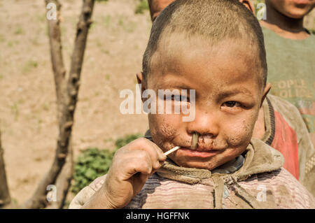 Dolpo, Nepal - circa May 2012: Young boy with dirt on his face has lollipop in his mouth in Dolpo, Nepal. Documentary - Stock Photo