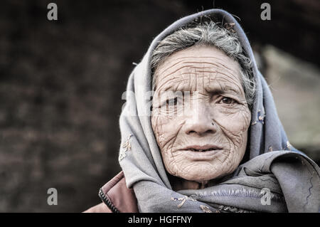 Dolpo, Nepal - circa May 2012: Old woman with wrinkles on her face and brown eyes wears grey headcloth in Dolpo, - Stock Photo