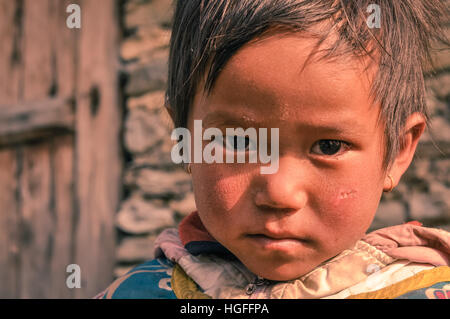 Beni, Nepal - circa May 2012: Small girl with short brown hair and brown eyes wears earrings and looks sadly to - Stock Photo