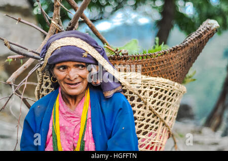 Beni, Nepal - circa May 2012: Native woman with blue headcloth and earrings carries basket on her back by using - Stock Photo