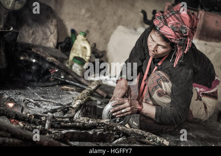 Dolpo, Nepal - circa May 2012: Native woman with red headcloth kneels next to wooden branches and works during preparation - Stock Photo