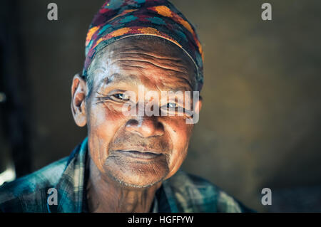 Beni, Nepal - circa May 2012: Native man with wrinkled face and colourful cap on his head in Beni, Nepal. Documentary - Stock Photo