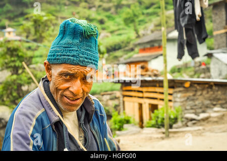 Beni, Nepal - circa May 2012: Old man with blue knitted cap on head has wrinkles on forehead in Beni, Nepal. Documentary - Stock Photo
