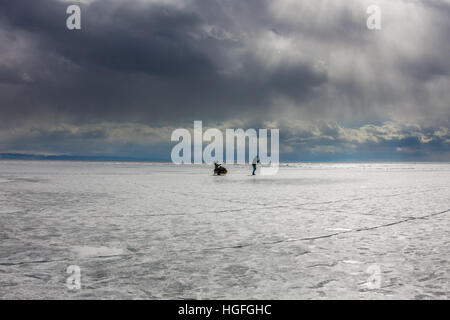 woman and a man with a sledge and trekking pole is ice of Baikal - Stock Photo