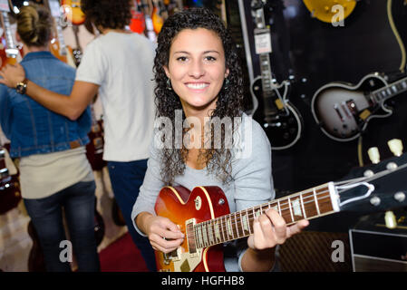 Young woman testing guitar in shop - Stock Photo