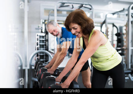 Senior couple in gym working out with weights - Stock Photo