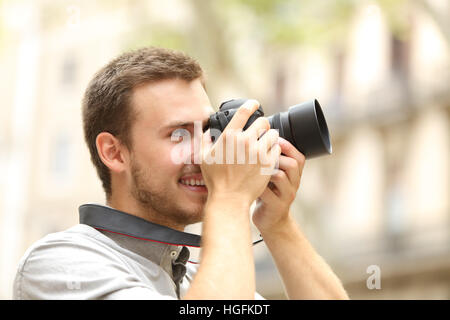 Side view of a happy man photographing with a dslr camera in the street of a city or town - Stock Photo