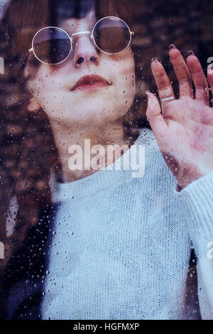 Portrait of a young woman in a rainy day through a window