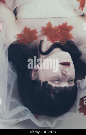 Young brunette woman lying on water with a white dress and red maple leaves - Stock Photo