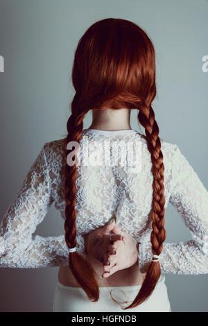 Young redhead woman with two long braids back to the camera - Stock Photo