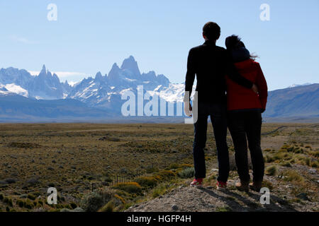Couple admiring view over Mount Fitz Roy and Cerro Torre, El Chalten, Patagonia, Argentina, South America - Stock Photo